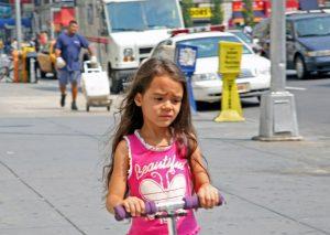 Foto: sorgenvoll betrübtes Mädchen auf einem Rollen in mitten einer Stadt