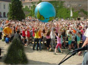 Viele Kinder spielen mit einem großen Erdball-Luftballon