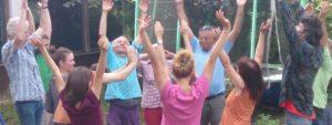 Foto: Menschen bei einem Singspiel, die die Arme nach oben strecken.