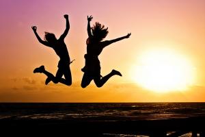 Foto: Schattenbild zweier Jugendlicher die am Strand einen Luftsprung machen