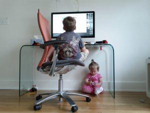 Foto: Ein Kind sitzt vorm PC am Schreibtisch, ein anderes sitzt unterm Schreibtisch