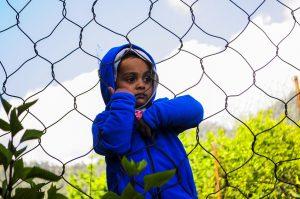 Foto: resigniertes Kind hängt am Maschendrahtzaun