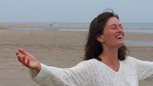 Foto: Luna am Strand, lachend mit ausgestreckten Armen
