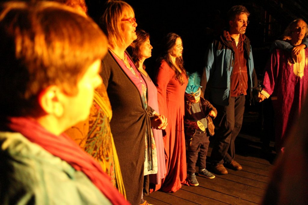 Foto: Alle singen andächtig im Kreis stehend beim Musik-Theater in Elsas Cafe