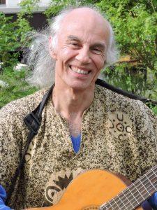 Foto: Porträt von Micha mit seiner Gitarre im Hochformat