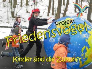 Foto: Micha rollt mit Kindern die Erdkugel durch die Schneelandschaft mit der Aufschrift: 'Projekt Friedensvogel - Kinder sind die Zukunft'
