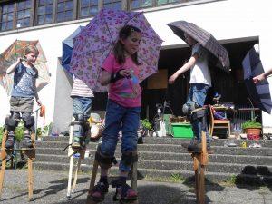 Foto: Kinder tanzen auf Stelzen mit aufgespannten Regenschirmen