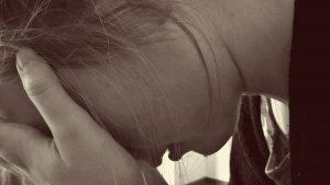 Foto: verzweifelte Frau, die ihr Gesicht in ihren Händen vergräbt