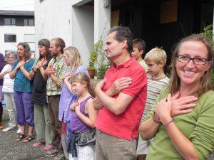 Foto: Menschen stehen gerührt im Kreis mit den Händen auf ihren Herzen