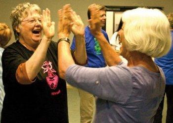 Foto: zwei ältere Damen lachend bei einem Klatschspiel